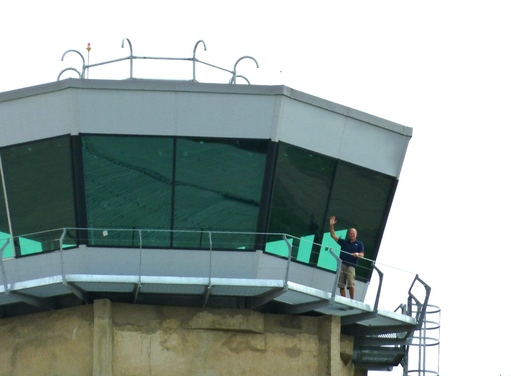 Tex ATC team member waves from the top of a standard off-the-shelf air craft control tower room